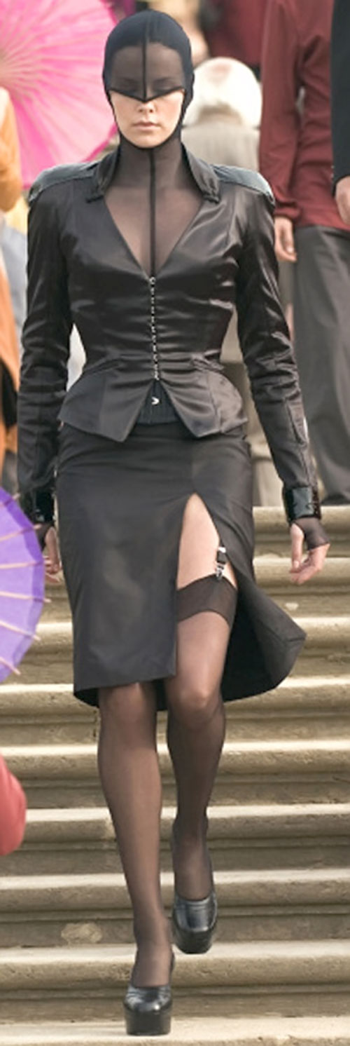Aeon Flux (Charlize Theron) in a futuristic black ensemble with a leather jacket
