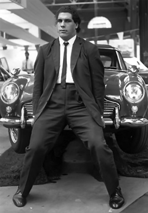 Andre the Giant (wrestler) in a suit lifts the front of a car