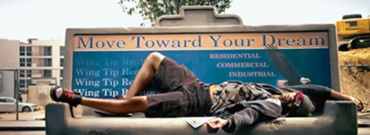 Hancock (Will Smith) lies on a concrete bench