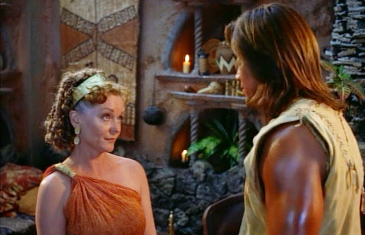 Hercules (Kevin Sorbo) discusses with a woman in an orange toga