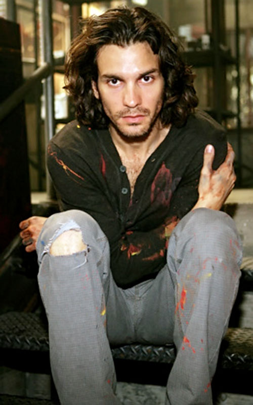 Isaac Mendez (Santiago Cabrera in NBC's Heroes) sitting with paint-stained clothes