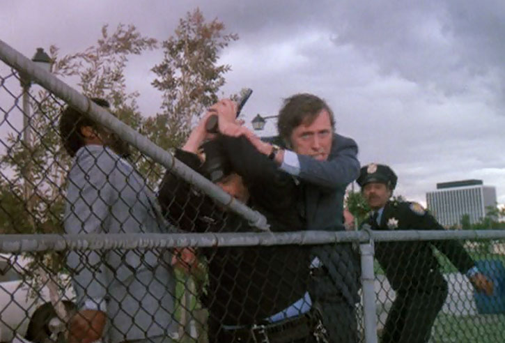 Jack McGee (Jack Colvin) tries to get past police officer