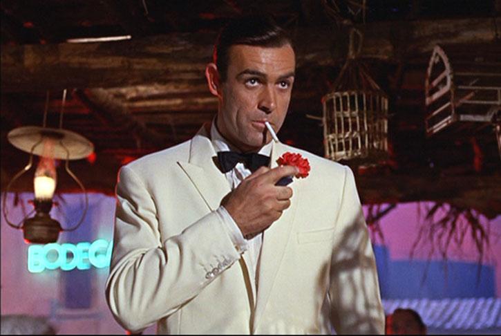 James Bond (Sean Connery) smoking in a white tuxedo