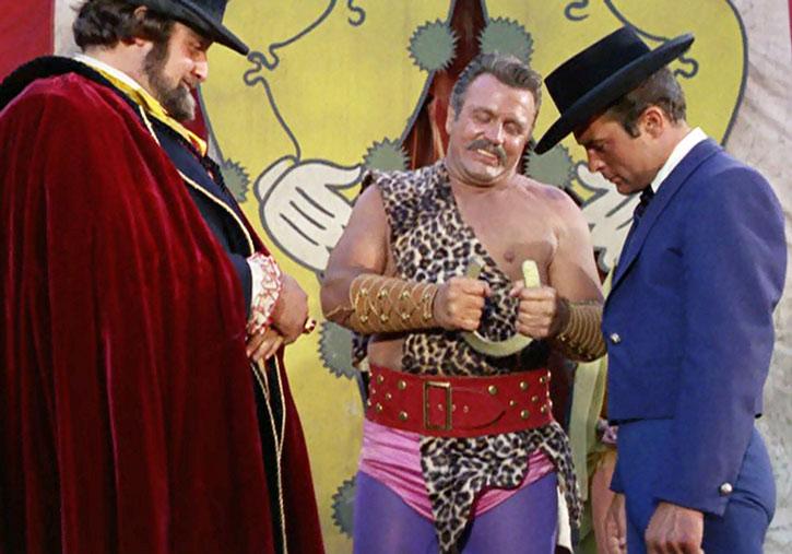 James West (Robert Conrad) watches a circus strongman
