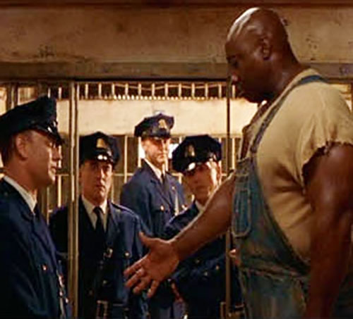 John Coffey (Michael Clarke Duncan in The Green Mile) (Stephen King) among guards, offering his hand