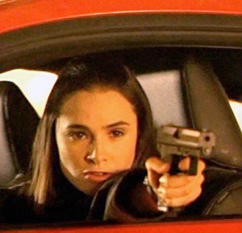 Nadia Santos (Mia Maestro in Alias) aiming a pistol