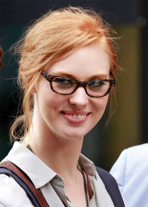 Deborah Ann Woll with glasses and a beige shirt