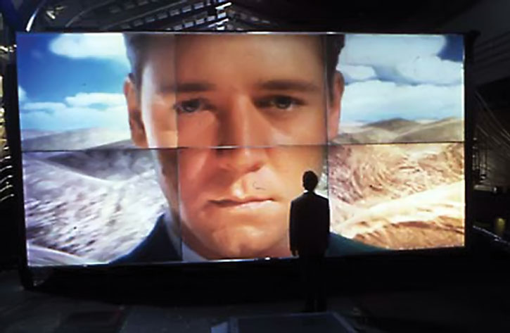 SID 6.7 (Russell Crowe)'s face ona wall of screens