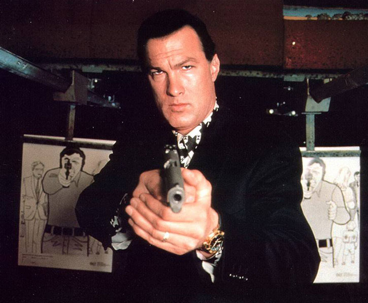 Steven Seagal pointing a pistol at the range