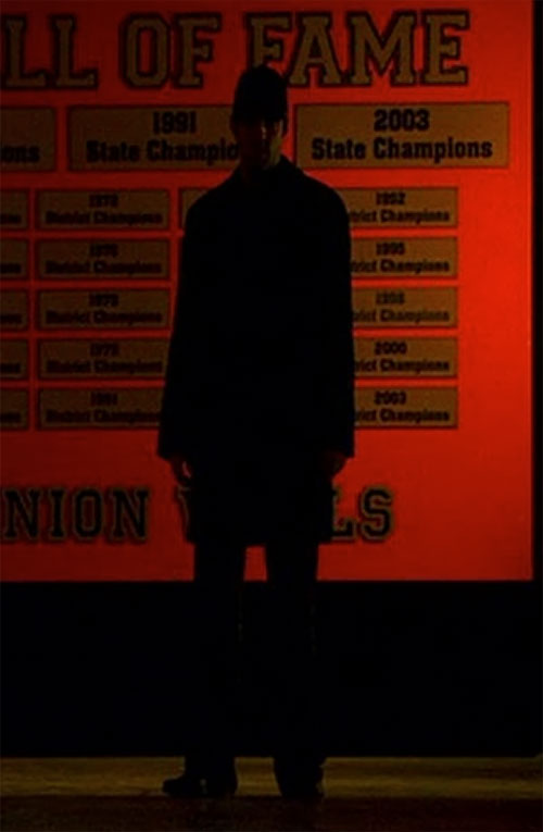 Sylar (Zachary Quinto in NBC's Heroes) in shadows before a sports trophy wall