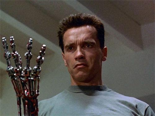The Terminator (Arnold Schwarzenegger) examines its robotic hand