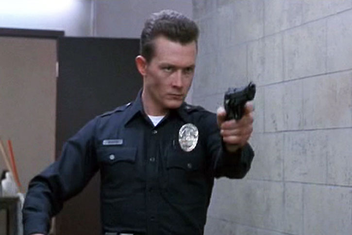 The T-1000 (Robert Patrick) in a police uniform aims a Beretta