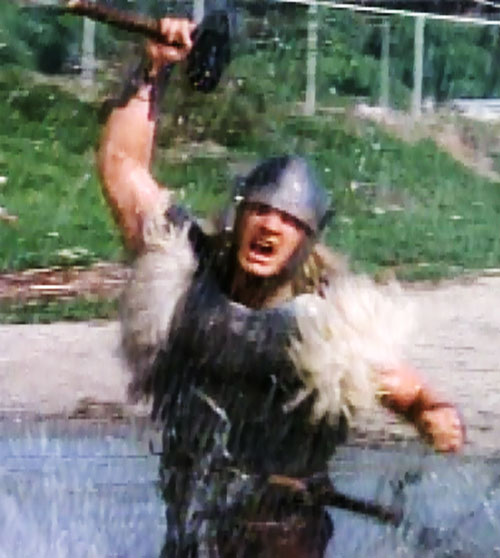 Thor (Eric Kramer in Incredible Hulk Returns) (Marvel movie) brandishes his hammer in a fountain