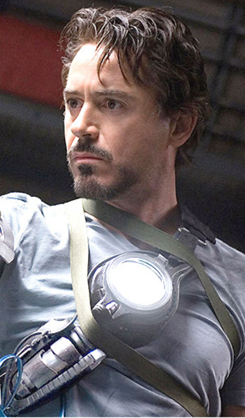 Iron Man (Robert Downey Jr. in the first Marvel movie) with a prototype arc repulsor strapped to his chest