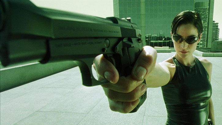 Trinity (Carrie-Anne Moss) points her pistol