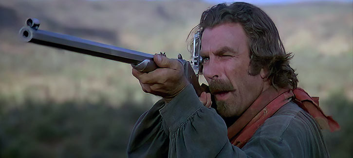 Tom Selleck aiming a Sharps rifle