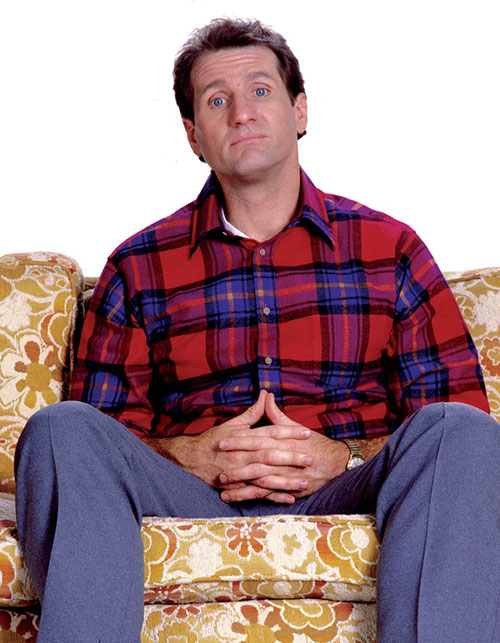 Al Bundy (Ed O'Neil in Married with Children) sitting on an ugly couch