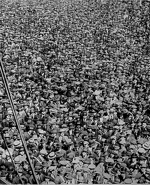 Old photograph of a crowd of men with hat