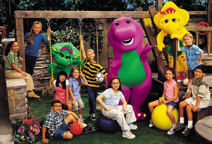 Barney the purple dinosaur with children and swings