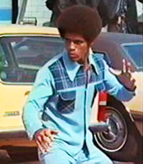 Jim Kelly as Black Belt Jones, in a blue polyester shirt