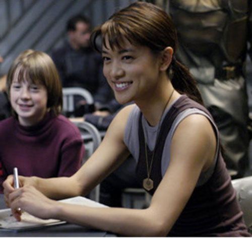 "Sharon ""Boomer"" Valerii (Grace Park in Battlestar Galactica) smiling and writing"