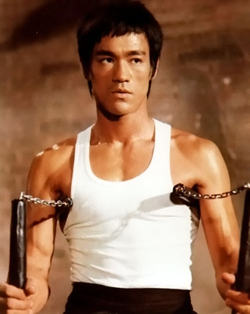 Bruce Lee in a tank top with paired nunchakus