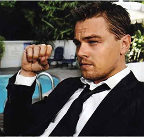 Dom Cobb (Leonardo di Caprio in Inception) in a black suit next to a pool