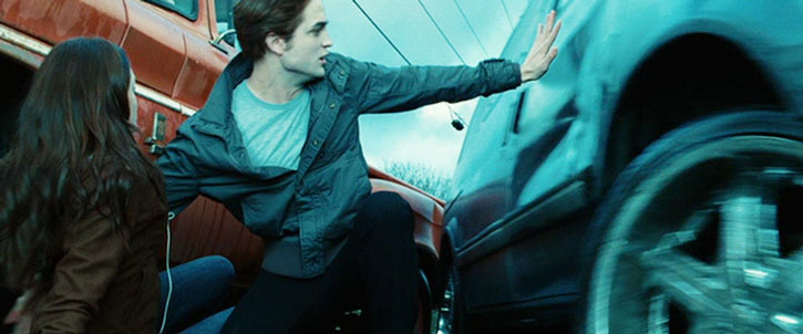 Edward Cullen (Robert Pattinson) pushes back a car