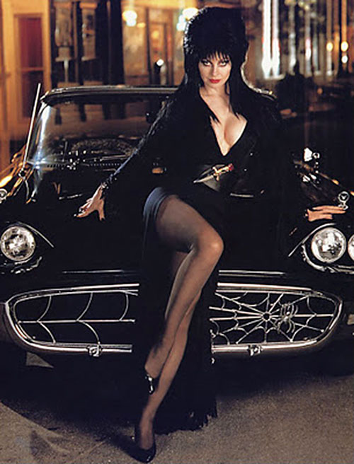 Elvira Mistress of the dark (Cassandra Peterson) sitting on her black custom car