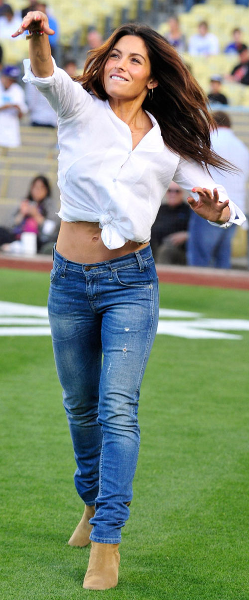 Sarah Shahi throwing a ball on a sports field, wearing jeans and a white blouse