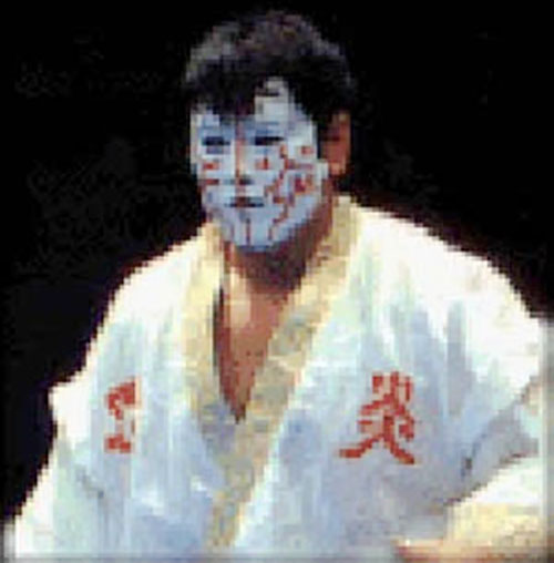 The Great Muta in a white vest and mask