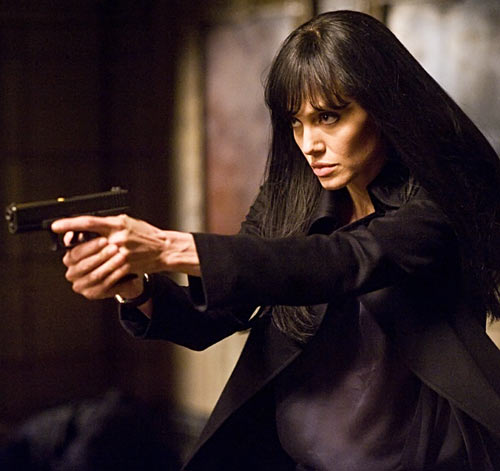 Angelina Jolie with long black hair and a handgun, in the movie Salt