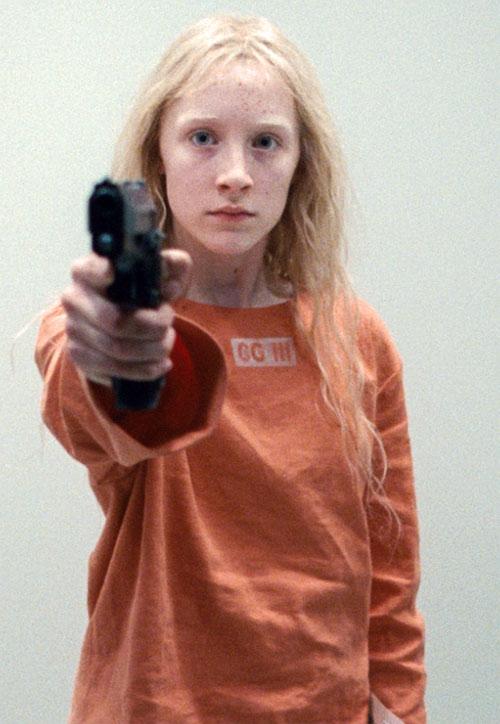 Hanna (Saoirse Ronan) in orange pointing a pistol