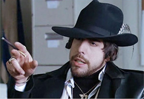 Mordechai Carver the Hebrew Hammer (Adam Goldberg) with a cigarillo and feathered hat