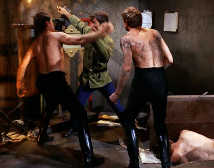 James West (Robert Conrad) fights two bare-chested men in tight pants