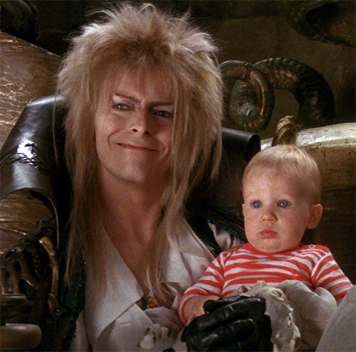 Jareth the Goblin King (David Bowie in Labyrinth) grinning with a baby