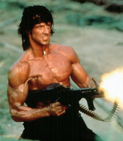 John Rambo (Sylvester Stallone) firing a machinegun one-handed