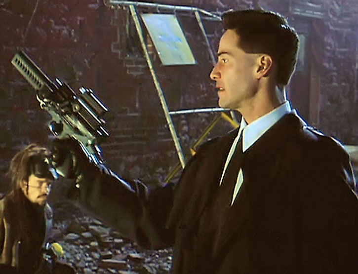 Johnny Mnemonic (Keanu Reeves) brandishes a pistol