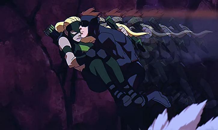 Kid Flash in a black costume, carrying Artemis