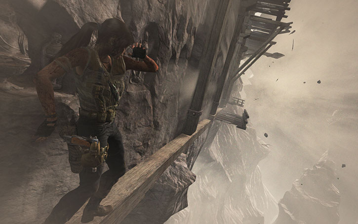 Lara Croft high up on a wind-swept ledge