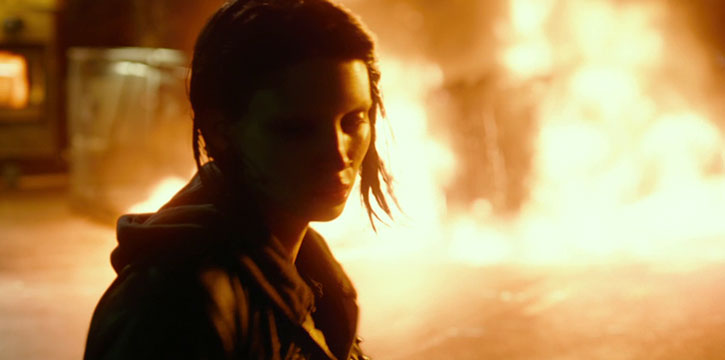 Lisbeth Salander stands before a fire