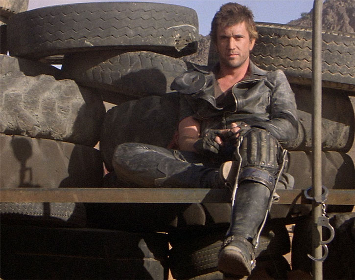 Mad Max (Mel Gibson) with a leg brace, sitting against a wall of tires