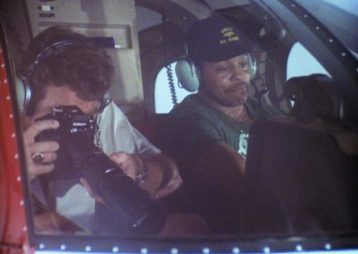 Magnum (Tom Selleck) taking photographs from a helicopter