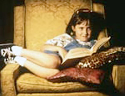 Matilda (Mara Wilson in Matilda) reading on an armchair