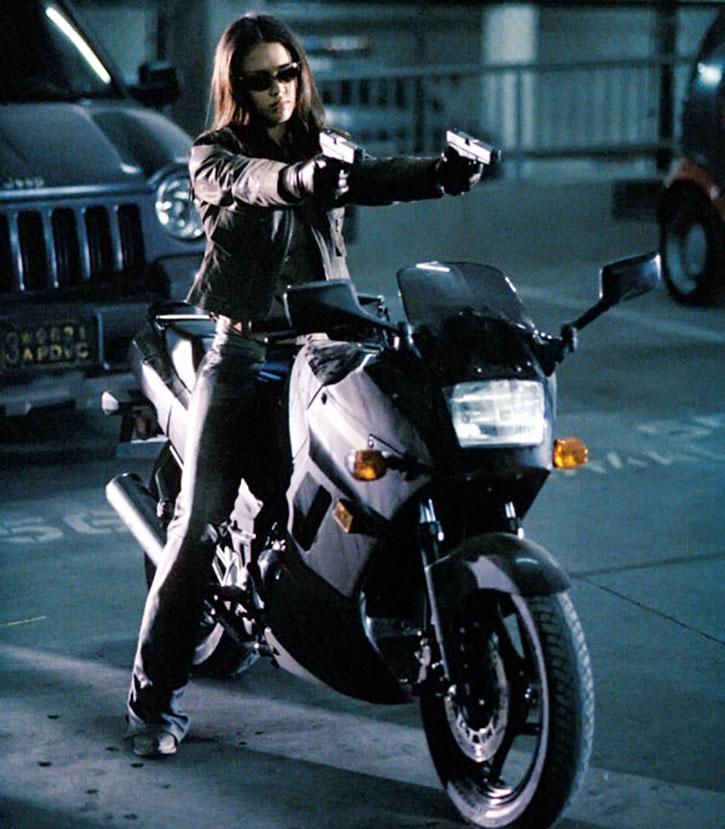 Max Guevara (Jessica Alba) dual-wielding pistols on her bike