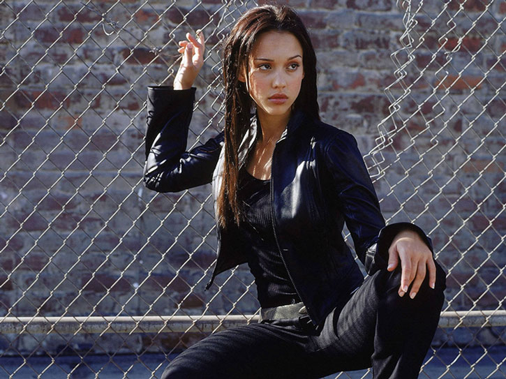 Max Guevara (Jessica Alba) in black, and a chain link fence