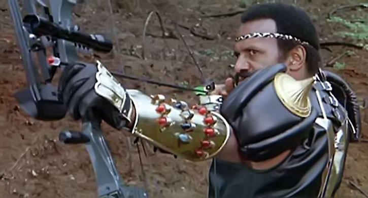 """Nadir (Fred """"the Hammer"""" Williamson) shooting his bow"""