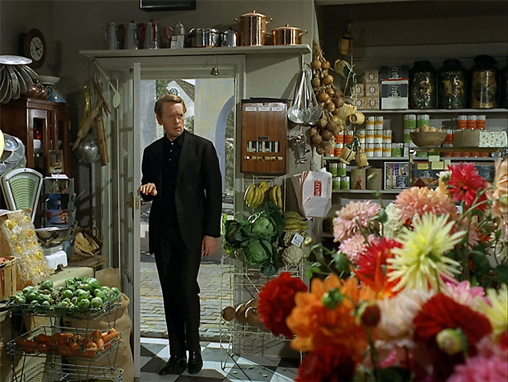 The Prisoner (Patrick McGoohan) enters a grocery