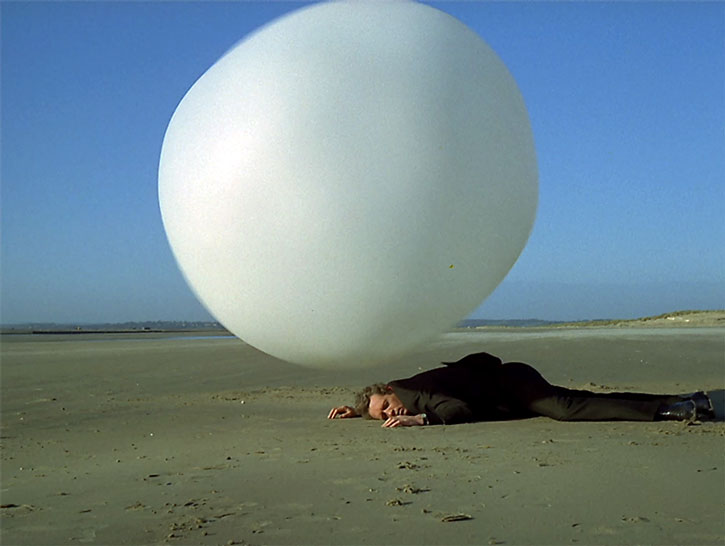 A rover capture device stands over the Prisoner (Patrick McGoohan) on a beach
