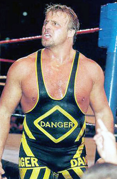 Owen Hart in a black and industrial yellow costume